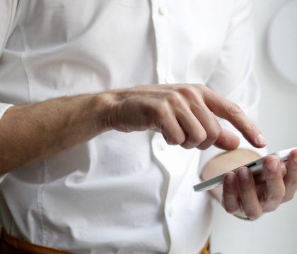 Mann mit weißem Hemd und Smartphone in der linken Hand